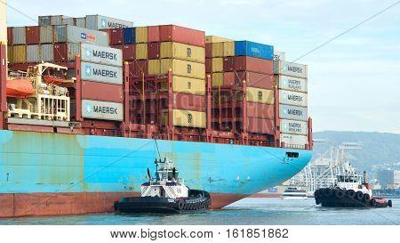 Oakland CA - December 13 2016: Tugboats REVOLUTION and VETERAN assist cargo ship GERD MAERSK maneuver into the Port of Oakland.