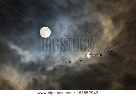 Passenger jet airliner makes non-stop night flight in the light of full moon to long-haul and long-range destination through storm clouds in turbulence conditions