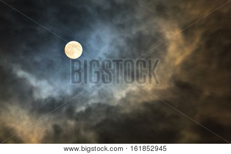 Mysterious midnight cloudy sky with full moon and backlit moonlight storm clouds