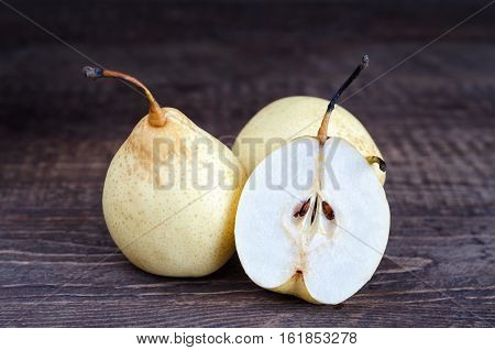 Pears, whole and half rests on a wooden surface. Selective focus, low key.