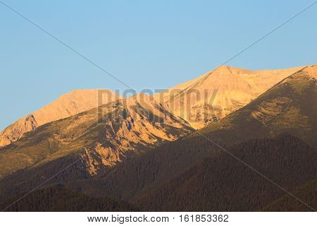 Morning sunrise view in glowing light of the Pirin Mountain and Vihren and Kutelo peaks from Bansko in summer a popular Bulgarian ski resort and tourist destination.