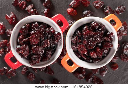 Two round bowls full od dried cranberries on a black slate plate top view