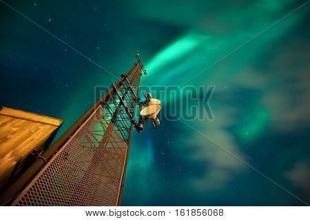 Antenna mast with great aurora borealis and stars in background Lofoten