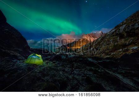 Green tent under green Aurora Borealis among snowy mountains of Moskenesoya Lofoten