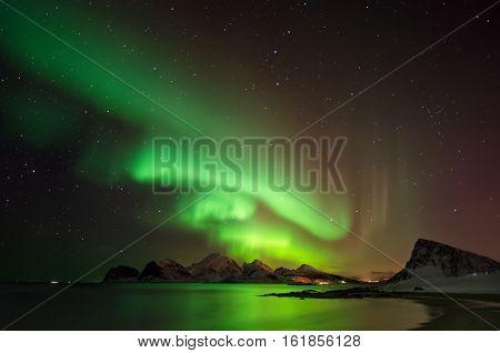 Aurora borealis above snowy island Vestvagoya Lofoten