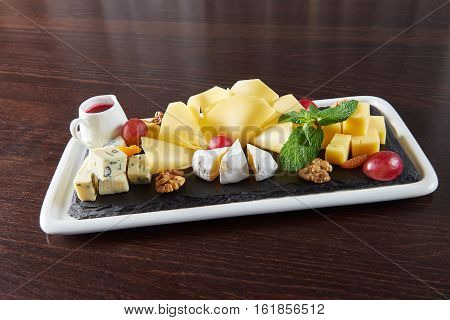Cheese love. Cheese plate with Dorblu Brie Gouda and Camembert on a plate served with walnuts and grapes on a restaurant table
