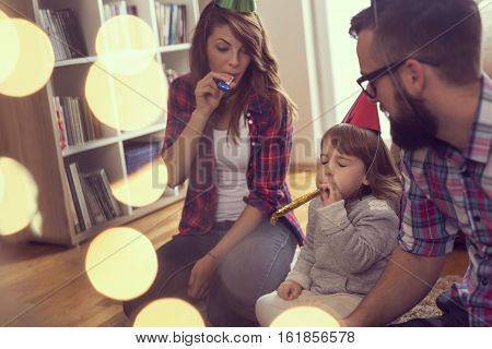 Beautiful young family sitting next to a nicely decorated Christmas tree wearing party hats and blowing party whistles. Focus on the baby girl