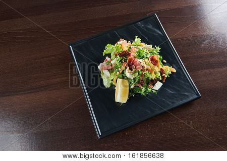 Healthy kitchen. Top view of a delicious prosciutto and arugula salad with dorblu cheese and pine nuts