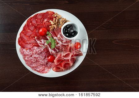 Salami appetizers. Sliced salami and ham of different kinds served on a plate with cherry tomatoes walnuts and black olives food concept top view copyspace