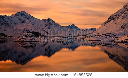 Orange sunset in fjord with snowy mountains in background, Lofoten