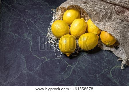 Fresh picked lemons spilling from a burlap sack. Horizontal format with copy space.