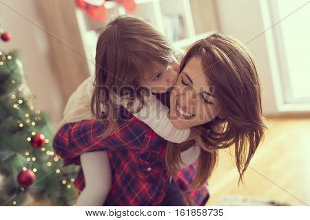 Mother giving her daughter a piggyback ride while daughter hugging and kissing her mother both having fun and enjoying winter holidays together. Focus on the mother