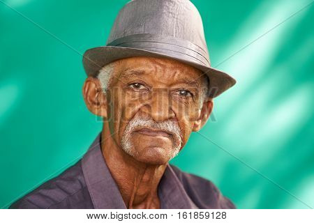 Real Cuban people and feelings portrait of sad senior hispanic man looking at camera. Worried old latino grandfather with mustache and hat from Havana Cuba