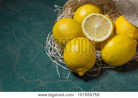 Fresh picked lemons spilling from a burlap sack close up. Horizontal format with copy space.