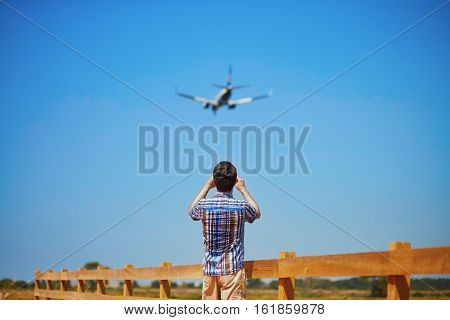 Man is looking at the glide path and landing plane or taking a photo of it. Aircraft spotting concept