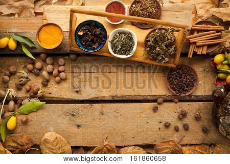 Ingredient for preparing healthy tea with spices and carnation, free space on wooden background, you can place your recipe.