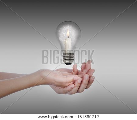 Broken Bulb With Candle Inside Levitates On Hands