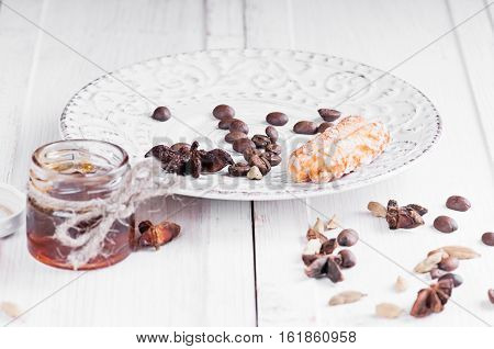 a small jar with honey on a vintage saucer decorated with seeds of anise and cardamom coffee with lace covers in the background