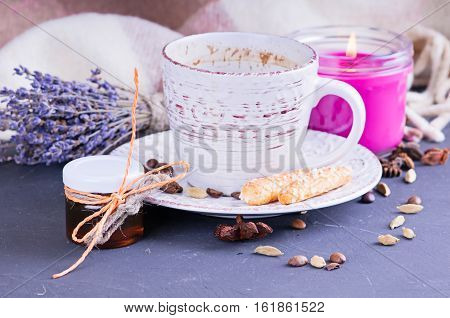 a vintage mug with hot coffee and spices decorated with a blanket in cage on a white wooden surface