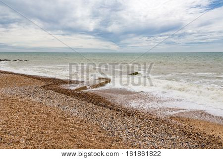 View of pebble beach with stong waves and a cloudy sky. Taken on a trip to Eastbourne in early summer.