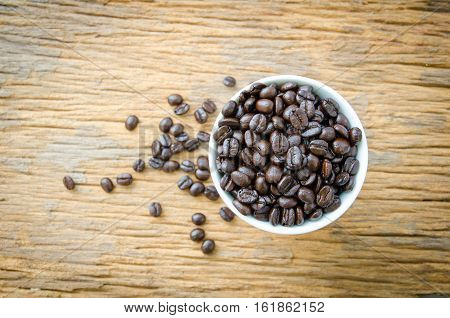 coffee beans on cup of wooden background