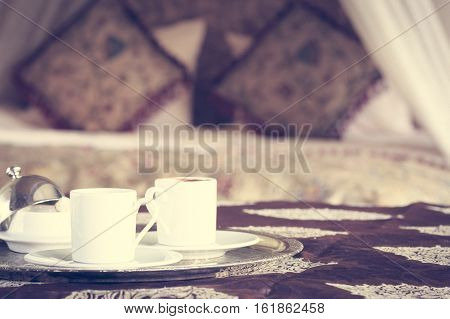 Two Turkish Coffee Cups With Oriental Canopy Bed At The Background