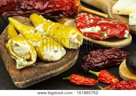 Detailed view of stuffed chillies. Preparing for the summer grill party. Dried chillies and spicy peppers filled with cheese. Delicacy suitable for grilled meats. Chillies and cheese.