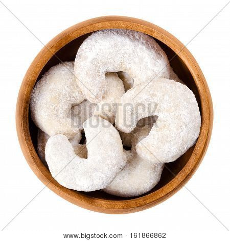 Crescent-shaped vanilla biscuits in wooden bowl. Vanilla almond half moons or Vanillekipferl, an christmas cookie scecialty from Austria. Isolated macro photo close up from above on white background.