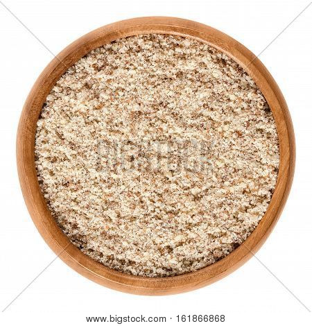 Ground almonds in wooden bowl. Ocher-colored powder of the light yellow raw edible seeds of Prunus dulcis. Isolated macro food photo close up from above on white background.