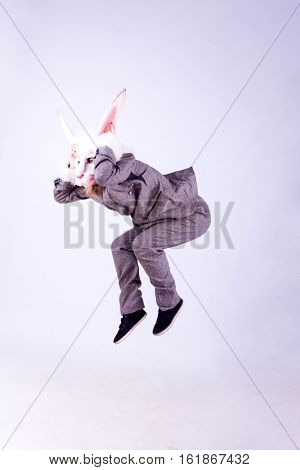 Young woman wearing the mask of rabbit posing isolated on white background