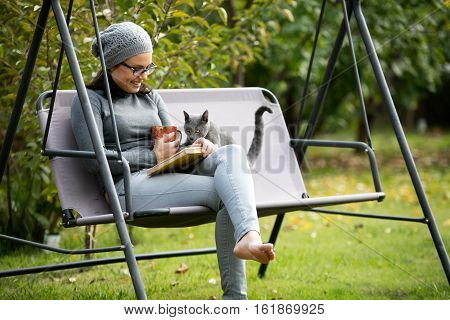 beautiful young woman reading a book, wearing vision glasses and holding a cup of tea