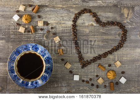 Coffee Cup coffee beans in the form of heart on a wooden table. Sugar gingerbread