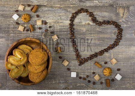 Coffee beans in heart shape on wooden table. Sugar carrot in a saucer