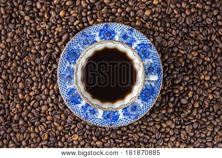 Coffee cup and saucer on a wooden table. Dark background. Blue saucer