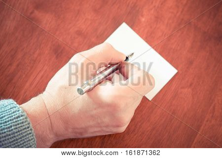 Hand writing with a fountain pen on a piece of paper on the brown wooden table