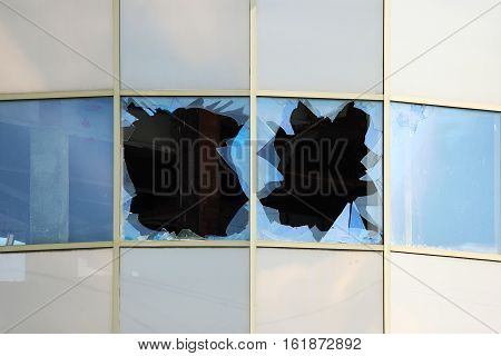 vandal broken windows in an abandoned shopping center building that stands unguarded