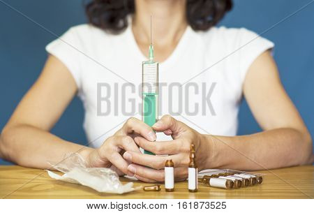 Woman holding a syringe with the vaccine for protection against flu