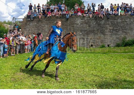 Koporje, Leningrad region, Russia - July 21, 2012: Reconstruction of knightly duels and battle chivalrous life camp, tents. Equestrian knight rides in a circle.