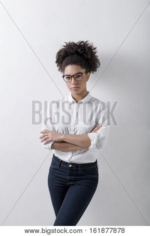 Young female entrepreneur standing at wall indoors