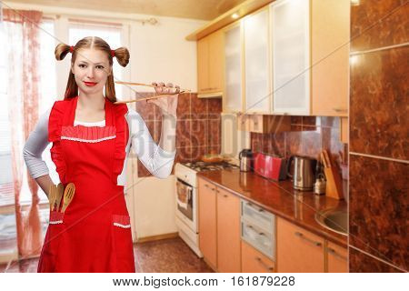 Young beautiful attractive smiling housewife in bright red apron with funny ponytails stand in kitchen and holds wooden salad tongs with wooden spoons and fork in pocket.