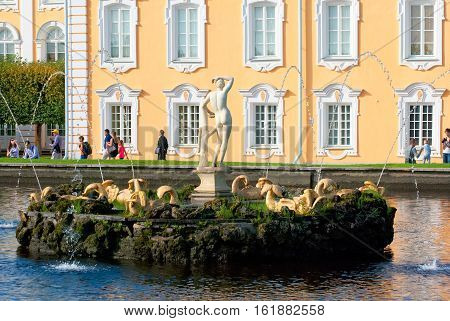 PETERHOF, SAINT - PETERSBURG, RUSSIA - AUGUST 19, 2016: The Upper Garden. People near Eastern Square Pond Fountain and Apollo Sculpture next to The Grand Palace