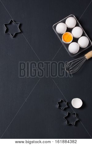 Dark wooden baking background with eggs whisk eggshell and star shape cookie cutter. Vertical orientation with copyspace top view.