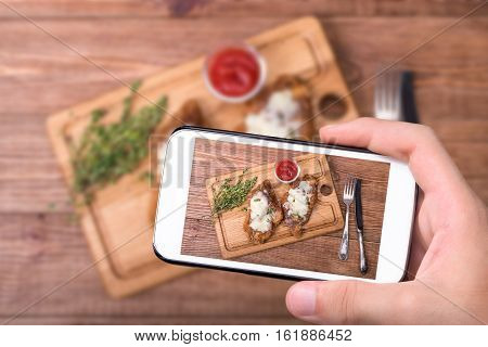 Hands taking photo baked chicken parmesan with smartphone.