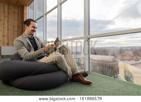 Business Man Using Cell Smart Phone Sit in front Panoramic Window Businessman In Coworking Center Office Interior