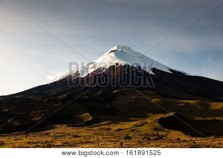 Volcan Cotopaxi at dawn the sun shines on its slopes gradually
