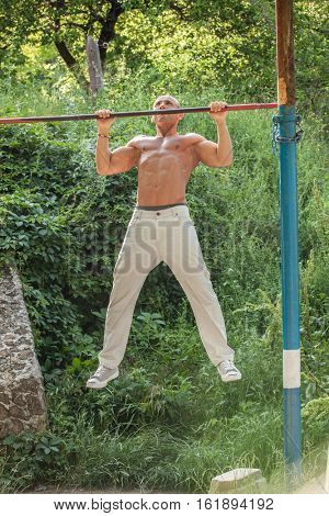 athlete doing pull-up on horizontal bar.Mans fitness with blue sky in the background and open space around him