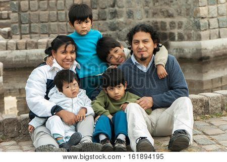 Happy Latin family sitting in the street