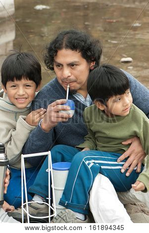 Portrait Latin family sitting in the street drinking mate