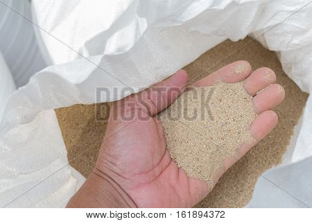 hand holding construction fine sand in white bag