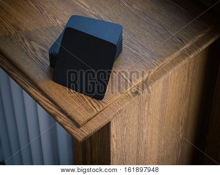 Stack of black square beer coasters on wooden windowsill. 3d rendering